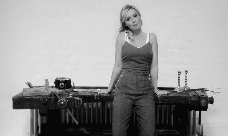 Frau im schulterfreihem Jeansanzug vor Workbank